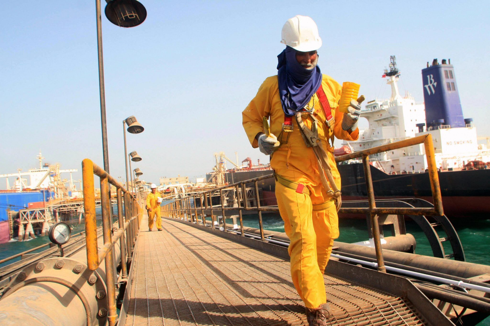 Iraqi oil workers walk on the dock of th
